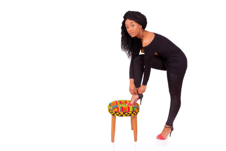 sitting pretty: Beautiful African American woman putting her high heels shoes