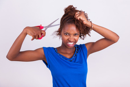 frizzy: Young African American woman cutting her frizzy afro hair with scissors - Black people