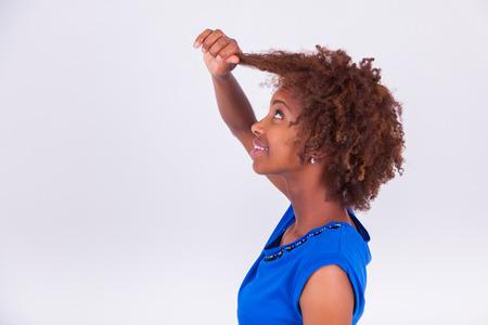 hair curly: Joven mujer afroamericana celebración de su pelo muy rizado afro - los negros