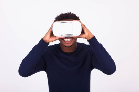 look latino: African American young man wearing vr virtual reality headset over white background Stock Photo