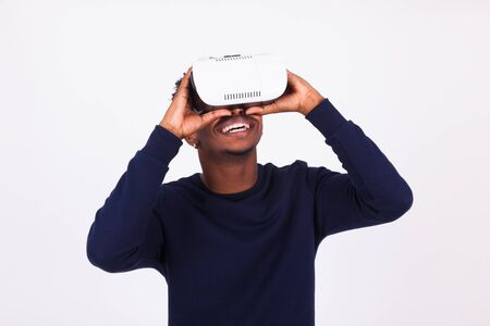 visualizing: African American young man wearing vr virtual reality headset over white background Stock Photo