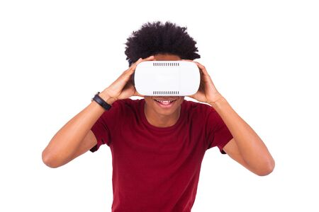 experiencing: African American young man wearing vr virtual reality headset over white background Stock Photo