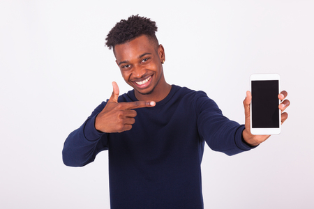 showing: Young African American man pointing his  smartphone screen - Black teenager people