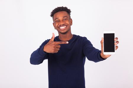그의 스마트 폰 화면 - 검은 십 대 사람들을 가리키는 젊은 아프리카 계 미국인 남자 스톡 콘텐츠
