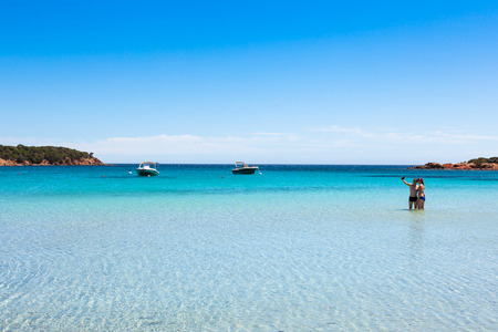Boats mooring in the turquoise water of  Rondinara beach in Corsica Island in France Stock Photo
