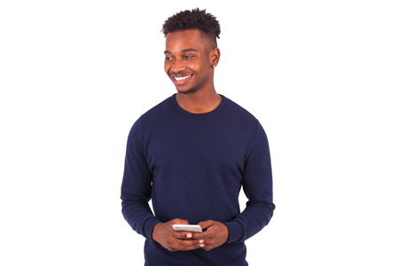 sms text: Young African American man sending a sms text message on his smartphone - Black teenager people Stock Photo