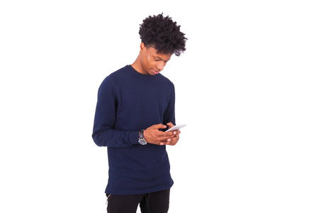 black guy: Young African American man sending a sms text message on his smartphone - Black teenager people Stock Photo