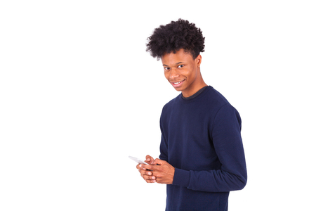 persone di colore: Young African American man sending a sms text message on his smartphone - Black teenager people Archivio Fotografico