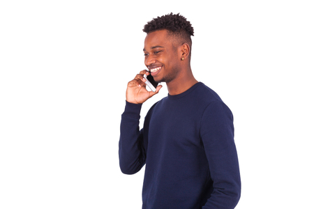 afro caribbean: Young African American man making a phone call on her smartphone - Black teenager people Stock Photo