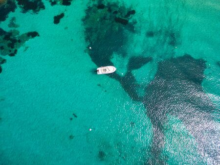 turquoise water: Aerial  view of a leisure boat mooring in translucent turquoise mediterranean sea water Stock Photo