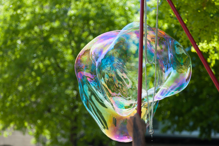 Arstist blowing colorful giant soap bubbles outdoor Stock Photo