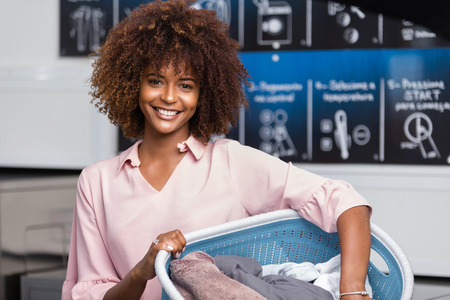Young black African American woman holding a basket of clothes to be washed in a automatic laundry