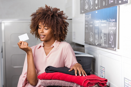 Young black African American woman holding a laundry subscription card Stockfoto