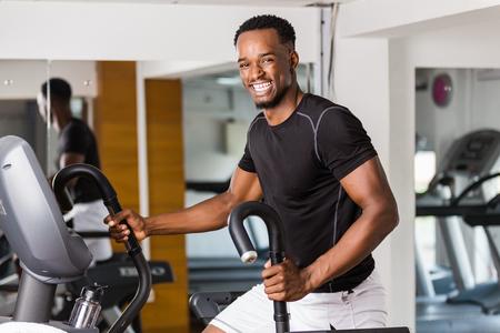 Schwarzer afroamerikanischer junger Mann, der im Fitnessstudio Cardio-Training macht Standard-Bild