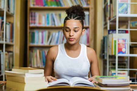 Black african american young girl student studying at the school university library Imagens - 124989671