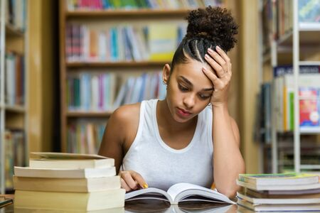 Black african american young girl student studying at the school university library Imagens - 124989685