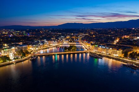 Aerial night view of Geneva city waterfront skyline in Switzerland
