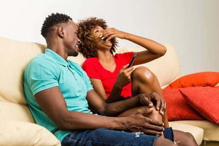 Black African American couple watching tv in the living room