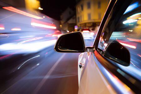 Sentier lumineux de voiture en conduisant dans le coty de nuit