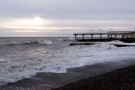 A pier on the coast against the backdrop of a raging sea in sunny weather.