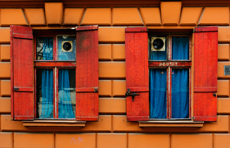 red shutters: two old windows  with red shutters in the stone wall