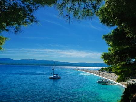 turquoise water: Beautiful beach Zlatni Rat in Croatia with a yacht