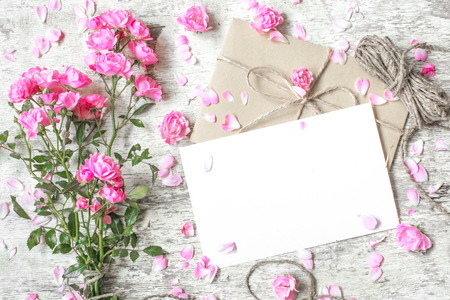 blank white greeting card with pink roses bouquet, buds with petals around and vintage rope with copy space