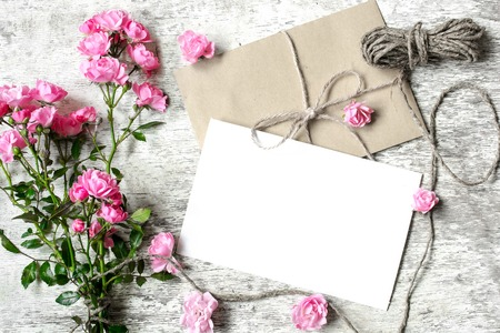 blank white greeting card with pink roses bouquet with a rope and envelope with flower buds on white wooden background
