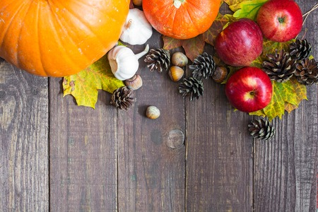 pinecones: harvest or thanksgiving background with autumnal fruits and vegetables with autumn leaves on wooden board