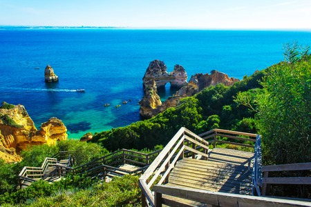 Wooden walkway to beautiful beach Praia do Camilo with cliff and rock formation, Algarve region, Portugal Stock Photo