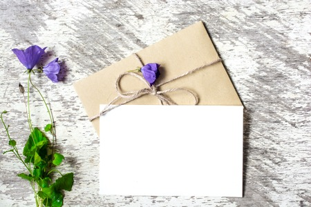 greeting card and envelope with wildflowers bouquet on white rustic background with copy space. holiday background