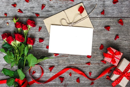 blank white greeting card and envelope with red roses flowers and red ribbon with gift boxes over rustic table. mock up. valentines day background Imagens