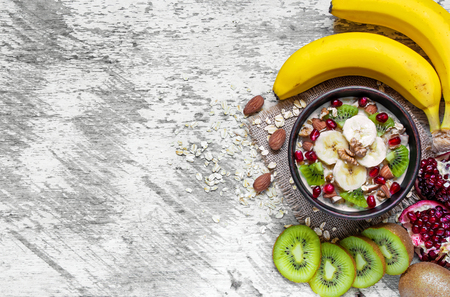 oatmeal porridge with banana, kiwi fruit, pomegranate and nuts in a bowl on white wooden background. healthy breakfast. top view