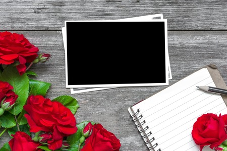 blank photo frame with red rose flowers bouquet and lined notebook on rustic wooden background. top view. mock up. flat lay. valentines day background