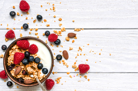 bowl of oat granola with yogurt, fresh raspberries, blueberries and nuts with spoon on white wooden board for healthy breakfast, top view