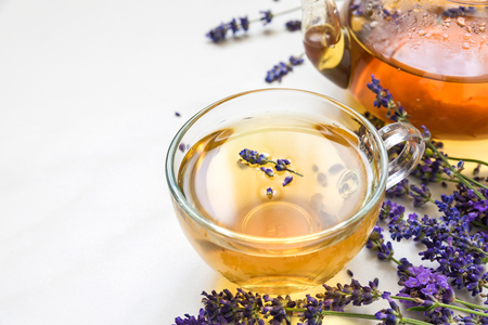 cup of lavender tea and teapot with fresh flowers over white marble table. herbal drink. close up with copy space Banque d'images