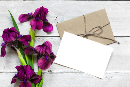 blank white greeting card with purple iris flowers bouquet and envelope on white wooden background. flat lay. top view. mock up