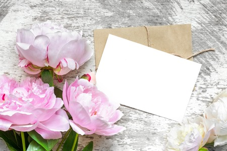 blank white greeting card with pink peony flowers bouquet and envelope on white wooden background. flat lay. top view. mock up 免版税图像