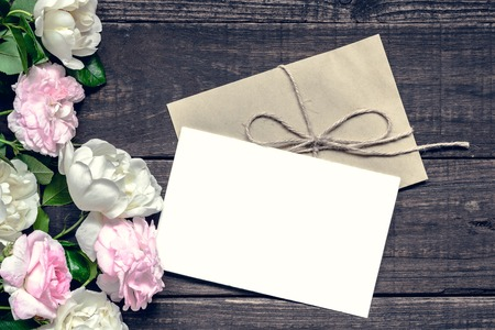 Stylish branding mockup to display your artworks. vintage wedding greeting card with pink and white roses mock up on wooden background. mothers background. vintage toning Stock Photo