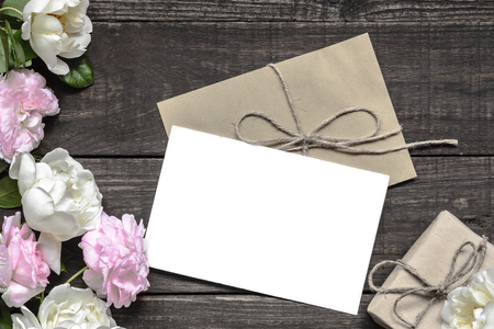 Stylish branding mockup to display your artworks. vintage wedding greeting card with pink and white roses and gift box mock up on wooden background. mothers background