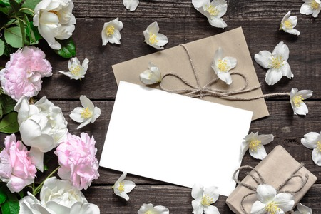 blank white greeting card with pink and white roses in frame made of jasmine flowers with gift box over rustic wooden table. flat lay. top view Stock Photo