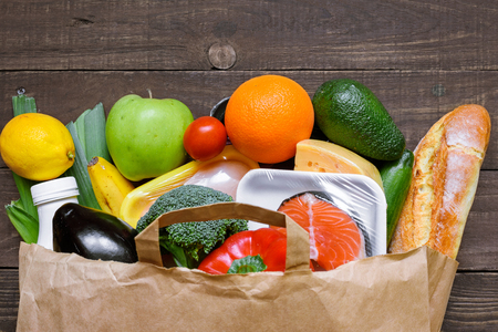Different food in paper bag on rustic wooden background. close up. Grocery shopping concept. top view Foto de archivo