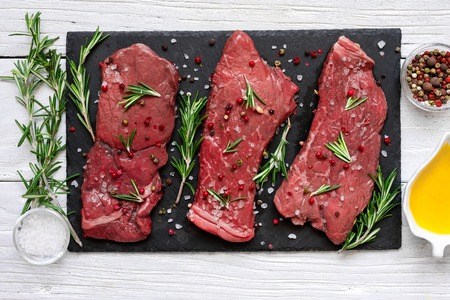 Raw meat, beef steak with spices, olive oil and rosemary on black slate cutting board over wooden background. top view