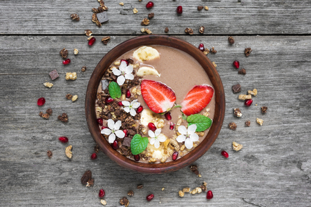 bowl of choclate and banana smoothie with chocolate granola, strawberry and pomegranate seeds decorated with flowers. top view. healthy breakfast