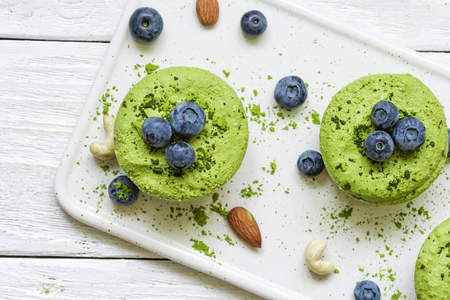 green matcha vegan raw cakes with blueberries, mint and nuts. healthy delicious food. top view 免版税图像