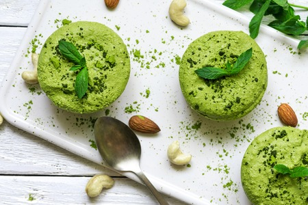 green matcha vegan raw cakes with mint and nuts. healthy delicious food. top view