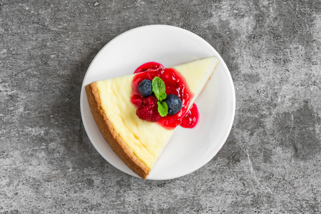 slice of cheesecake with fresh raspberries, blueberries, jam and mint on concrete background. top view. tasty breakfast