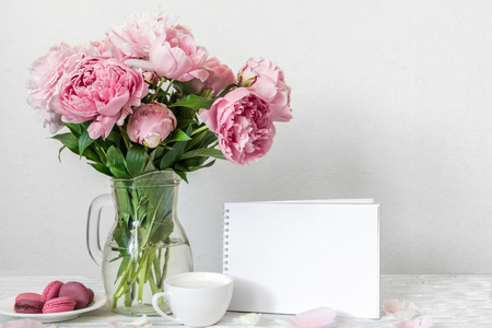 Still life with bouquet of pink peony flowers, blank greeting card, cup of cappuccino and macaroons. mock up. holiday or wedding background. high key