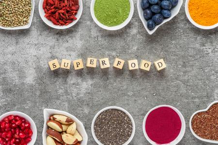 Superfood as acai powder, turmeric, matcha green tea, pumpkin and chia seeds, blueberry, goji berries, hemp and pomegranate seeds on dark concrete background. vegan food concept. top view Stock Photo