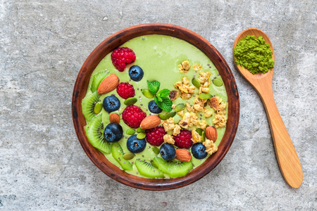 Smoothie bowl made of matcha green tea with fresh berries, nuts, seeds with a spoon for healthy vegan vegetarian diet breakfast. top view. flat lay